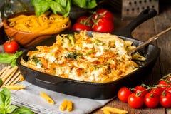 与硬花甘蓝、花椰菜、乳酪和调味酱sauc的被烘烤的面团 免版税库存照片