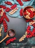 与碗和烹调匙子的红色和白色无核小葡萄干莓果在土气背景,顶视图,框架 热化和戒毒所 库存图片
