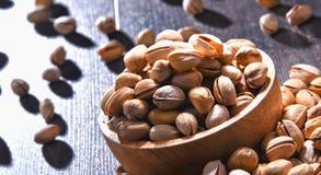 与碗的构成在木桌上的开心果 纤巧 图库摄影
