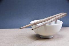 与碗的筷子在灰色背景 免版税库存图片