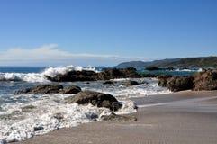 与碰撞的波浪的岩石海岸线 免版税库存图片