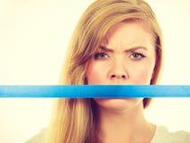与磁带的有吸引力的白肤金发的妇女覆盖物嘴 免版税图库摄影