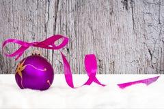 与磁带的紫色圣诞节球在灰色背景 库存图片