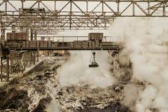 与磁性吊车的冶金热的炉渣转储 库存照片