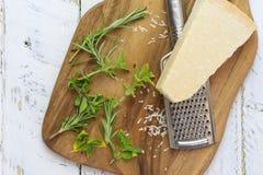与磨丝器的巴马干酪棋在砧板和新鲜的草本 免版税库存照片