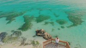 与礁石的美丽的浅绿色的海岸和在阳台的一对爱恋的夫妇在海滩上 美好的本质的 股票视频
