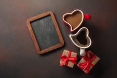 与礼物、一个心形的箱子、咖啡,心形的曲奇饼、蛋白杏仁饼干和黑板的情人节 顶视图与 库存照片