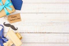 与礼物、领带和装饰旁边边界的愉快的父亲节礼物标记在白色木头 免版税库存图片