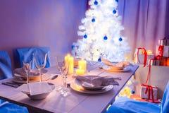 与礼物和树的华美的圣诞节桌设置 免版税库存图片