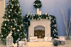 与礼物和火地方的装饰的圣诞树 库存照片