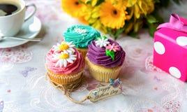 与礼物和花的母亲节杯形蛋糕 免版税库存图片