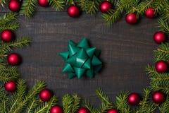 与礼物弓和圣诞节的黑暗的土气木桌背景 库存照片