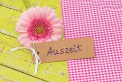 与礼物标记和德国词, Auszeit,手段暂停的桃红色雏菊大丁草花或放松 图库摄影