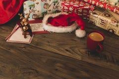 与礼物的圣诞老人木桌,包装纸,红色杯子用咖啡,圣诞节帽子 免版税库存照片