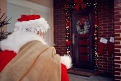 与礼物的圣诞老人运载的袋子在夜 免版税库存照片