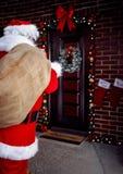 与礼物的圣诞老人运载的袋子孩子的在夜 库存照片