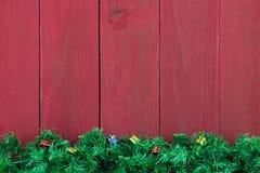与礼物的圣诞节常青树诗歌选边界由古色古香的红色木背景 库存图片