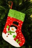 与礼物的圣诞节袜子在木墙壁上 库存图片
