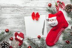 与礼物的圣诞节袜子 圣诞节垂悬在灰色土气木背景的装饰长袜和玩具 库存照片