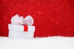 与礼物的在雪,红色背景,拷贝空间的圣诞卡和丝带 免版税库存图片