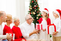 与礼物的微笑的家庭在家 库存照片