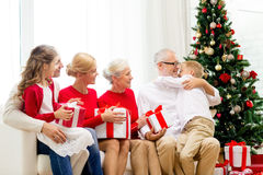 与礼物的微笑的家庭在家 库存图片