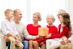 与礼物的微笑的家庭在家 免版税库存照片