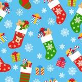 与礼物的无缝的样式圣诞节袜子在蓝色背景 库存例证
