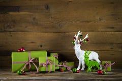 与礼物的欢乐圣诞节在红色a的背景和驯鹿 免版税图库摄影
