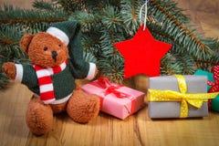 与礼物的玩具熊圣诞节、云杉的分支和红色星的 库存图片