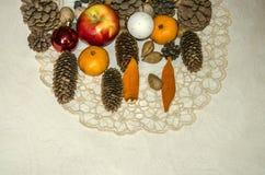 与礼物的被绣的餐巾从苹果,杏仁,蜜桔,坚果,有具球果锥体的圣诞节玩具的圣诞节的在胶合板 免版税库存图片