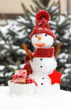 与礼物的装饰的雪人圣诞节或华伦泰的针叶树背景的盖了雪 库存照片