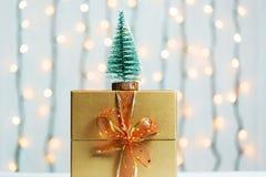 与礼物盒的一棵圣诞树在一个光亮garlandh和白板的被弄脏的bokeh横幅背景 圣诞快乐,想法 免版税库存照片