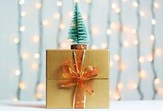 与礼物盒的一棵圣诞树在一个光亮garlandh和白板的被弄脏的bokeh横幅背景 圣诞快乐,想法 库存照片