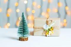 与礼物盒的一棵圣诞树在一个光亮garlandh和白板的被弄脏的bokeh横幅背景 圣诞快乐,想法 免版税图库摄影