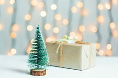 与礼物盒的一棵圣诞树在一个光亮garlandh和白板的被弄脏的bokeh横幅背景 圣诞快乐,想法 库存图片