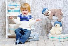 与礼物盒的微笑的孩子和玩具熊 免版税库存照片
