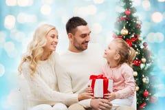 与礼物盒的愉快的家庭在圣诞灯 免版税图库摄影