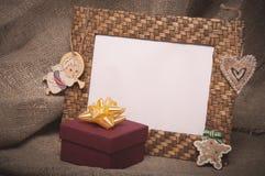 与礼物盒的桌面照片框架在亚麻制织品 库存照片