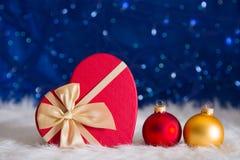 与礼物盒的红色和金黄圣诞节球在心脏o形状  免版税库存照片