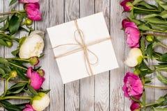 与礼物盒的美丽的花牡丹在轻的木背景 顶视图 图库摄影