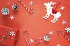 与礼物盒,装饰驯鹿,骗局的红色圣诞节背景 免版税库存照片