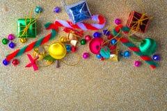 与礼物盒,雏菊花,糖果在葡萄酒金闪闪发光纸的球装饰的圣诞节和新年木背景横幅 免版税库存照片