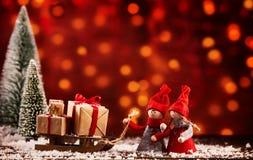 与礼物雪撬的两个逗人喜爱的圣诞节形象  免版税图库摄影