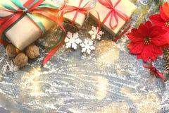 与礼物,箱子,锥体,核桃,一品红红色花的欢乐圣诞节构成在木背景的与白色sprin 图库摄影