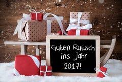 与礼物,雪花, Guten Rutsch 2017手段新年的雪橇 免版税库存图片