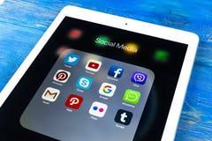 与社会媒介facebook, instagram,慌张,在屏幕上的snapchat应用象的苹果计算机iPad Proon蓝色木桌  Starti 库存图片