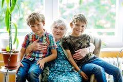 与祖母和两个孙子的愉快的家庭画象 在家坐与两个学校孩子男孩的盛大祖母 免版税库存图片