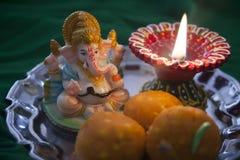 与祷告灯和Ganesha雕象的印地安甜laddu 免版税库存照片