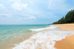 与离开的沙子海滩和白色的海景挥动 免版税库存图片